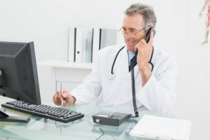 Smiling male doctor using computer and telephone at the medical office