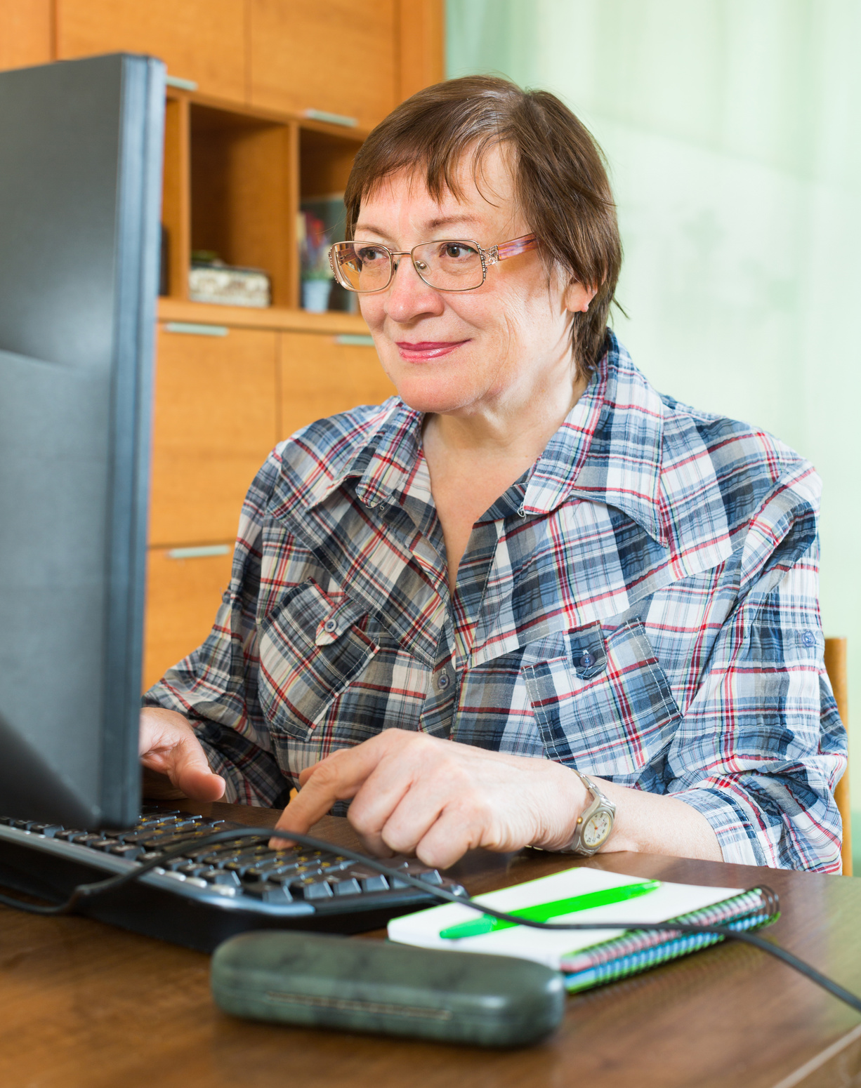 Smiling woman sitting in front of PC and using keyboard