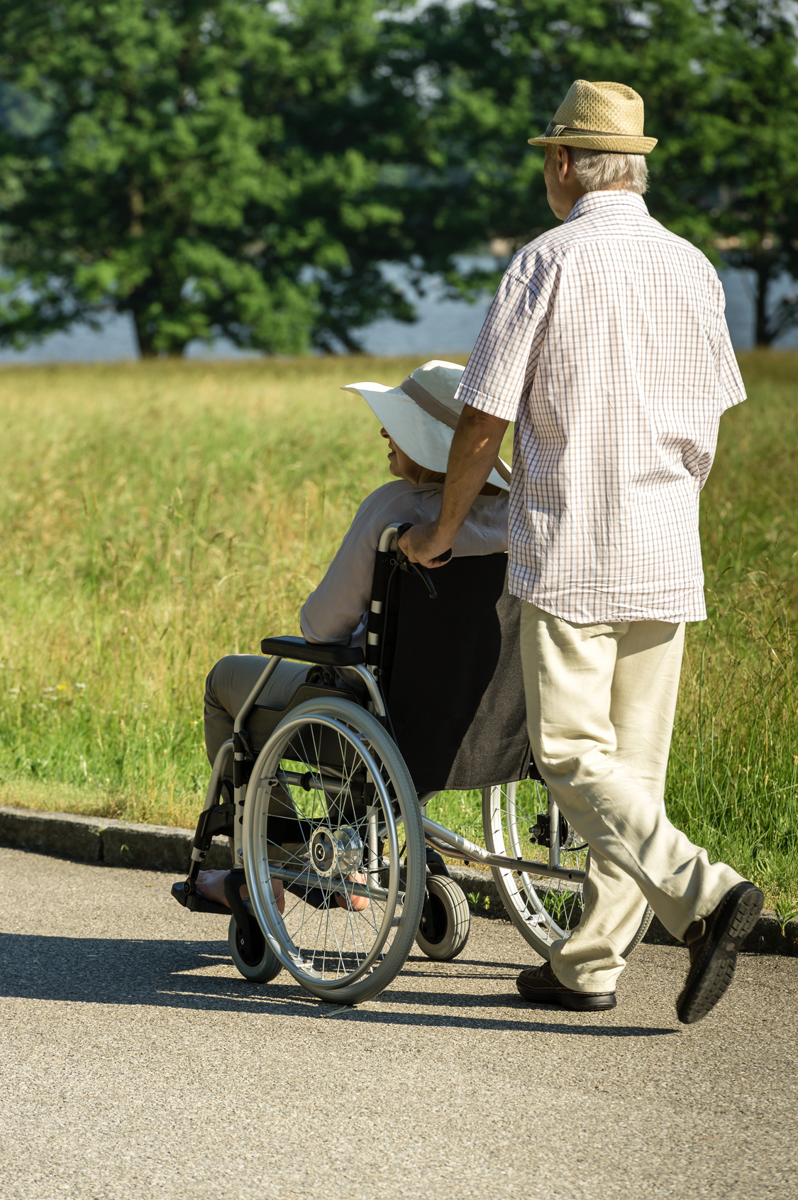 Senior husband pushing wife's wheelchair in park