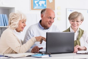 Photo of mature friends from learning group using laptop