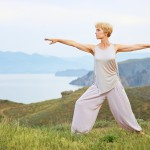 Senior woman doing yoga exercises with mountain on the background
